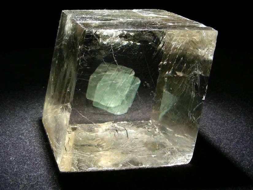 Avec l'octaèdre de fluorine verte placé derrière, on voit bien la biréfringence de la calcite optique ou spath d'Islande. © www.carionmineraux.com