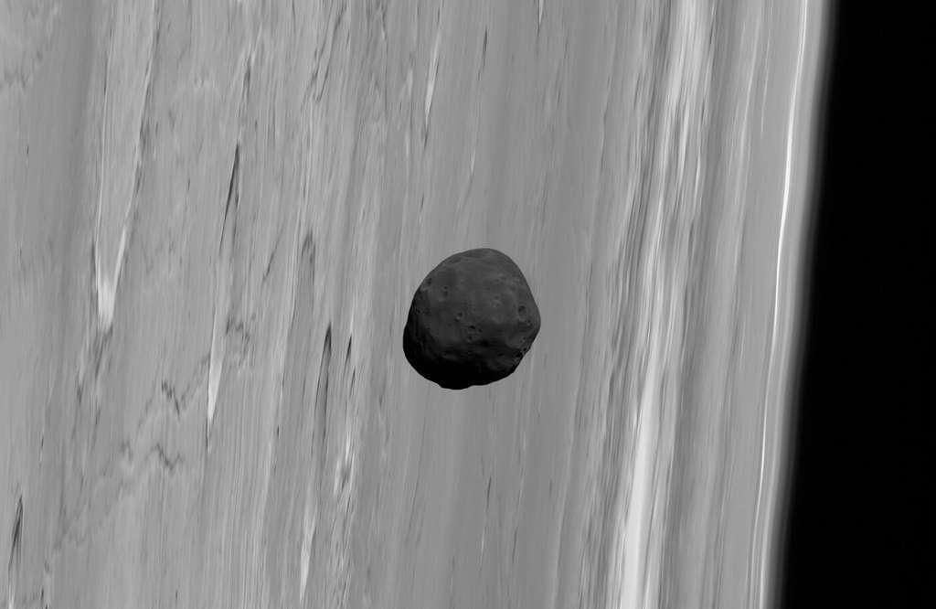 Phobos, un sombre satellite qui passe devant Mars. Il ressemble aux météorites à chondrites carbonées qui proviennent des régions les plus éloignées de la ceinture d'astéroïdes. Ce qui laisse à penser qu'il ne s'est pas formé en même temps que Mars ni à partir des mêmes matériaux. © G. Neukum (FU Berlin) et al., Mars Express, DLR, ESA