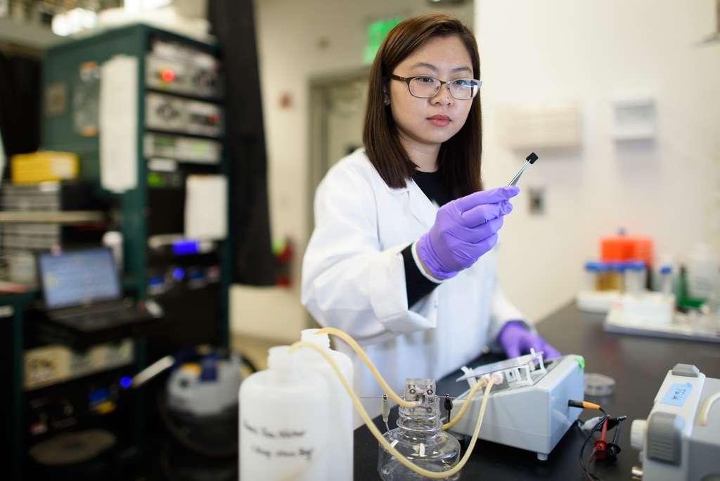 La chimiste Chong Liu examinant une électrode en carbone couverte d'amidoxime dans le cadre d'une recherche visant à améliorer l'extraction de l'uranium de l'eau de mer. © L. A. Cicero
