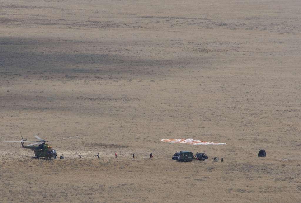 Dans les vastes steppes du Kazakhstan, une capsule Soyouz (à droite) posée au sol, après son atterrissage. © ESA, S. Corvaja