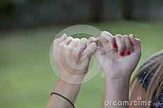 Description de photo: Deux jeunes filles avec des mains ont verrouillé dans la tige de promesse d'auriculaire avec le fond vert normal à l'extérieur