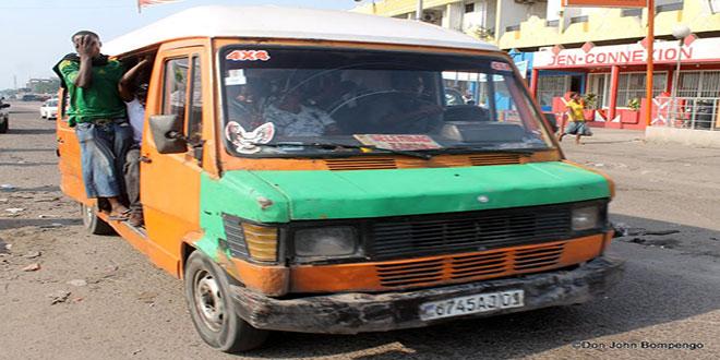 """Photo d'un receveur a la porte d'un bus communément appelée """"esprit de mort"""" en RDC."""