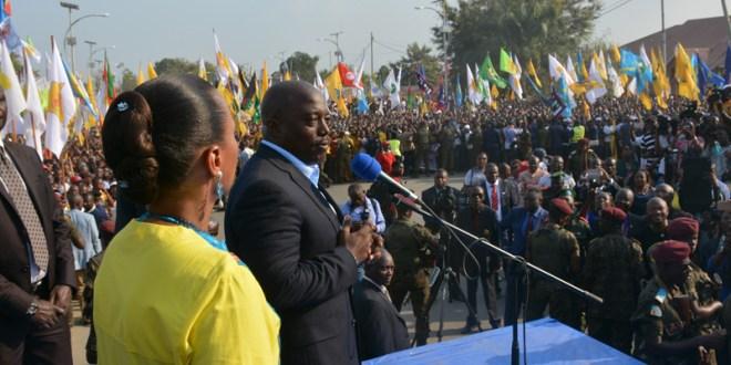 Photo d'un president congolais et sa femme a cote, en train de s'addresser a une foule.