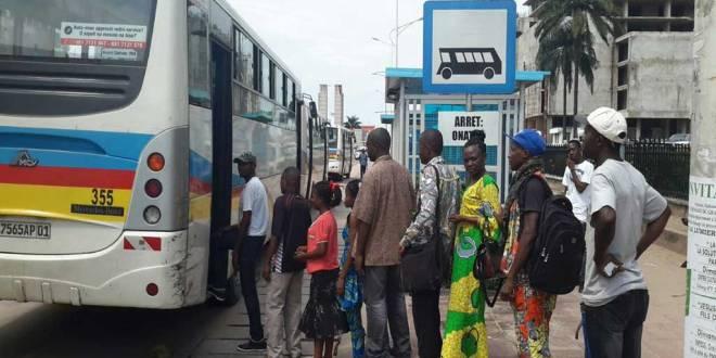 Des Congolais s'apprêtent à monter à bord d'un bus transco.