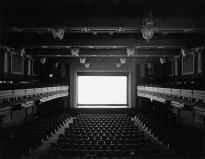 Black and white photograph of an empty theater displaying a glowing white screen