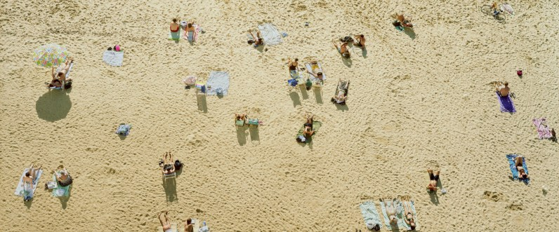 Color aerial photograph of beach-goers reclining on blankets on a sandy yellow beach