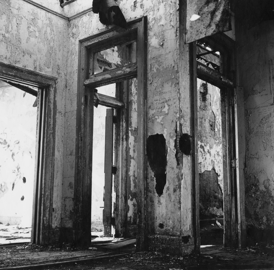 Black-and-white photograph of the view of crumbling walls through four meeting derelict doorways