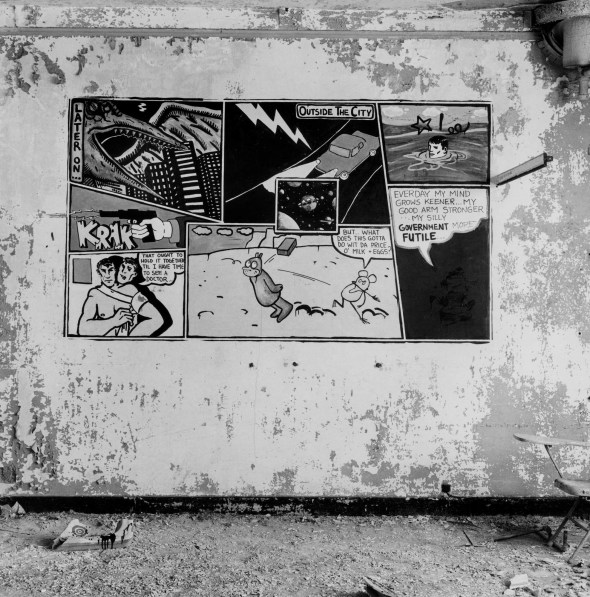 Black-and-white photograph of a derelict interior with comic panels painted on the wall