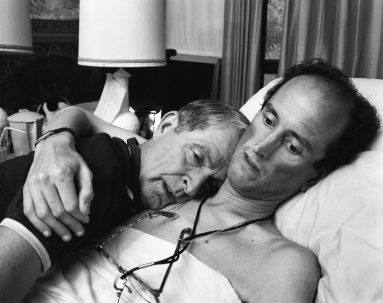 Black-and-white photograph of a young man in bed embracing an older man on his shoulder with one arm