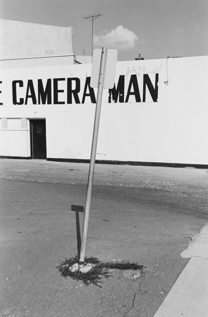 Black-and-white photograph of a street sign and a building with the text camera man painted on the side