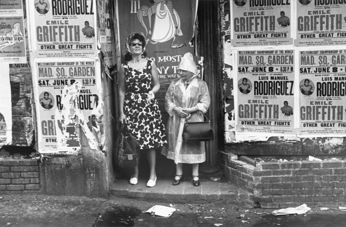 Black-and-white photograph of two women standing in a doorway of a building covered in boxing advertisements