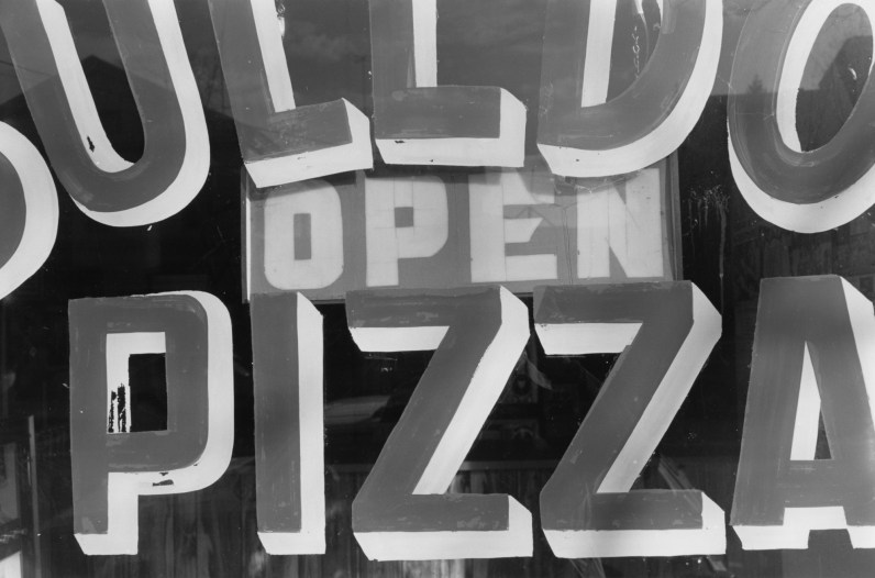 Black-and-white photograph showing detail of a sign with the text open pizza