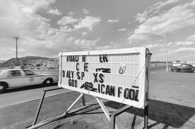 Black-and-white photograph of roadside sign missing letters with a police car speeding in the background and a cloudy sky