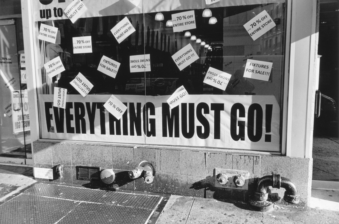Black-and-white photograph of a storefront with all caps text everything must go!