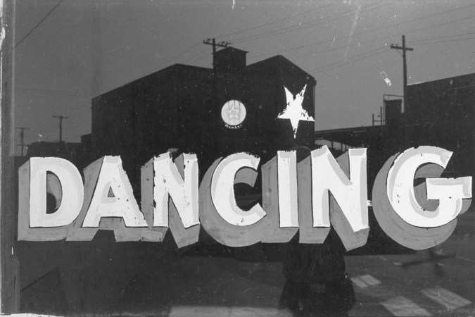 Black-and-white photograph of a hand painted sign with the text dancing
