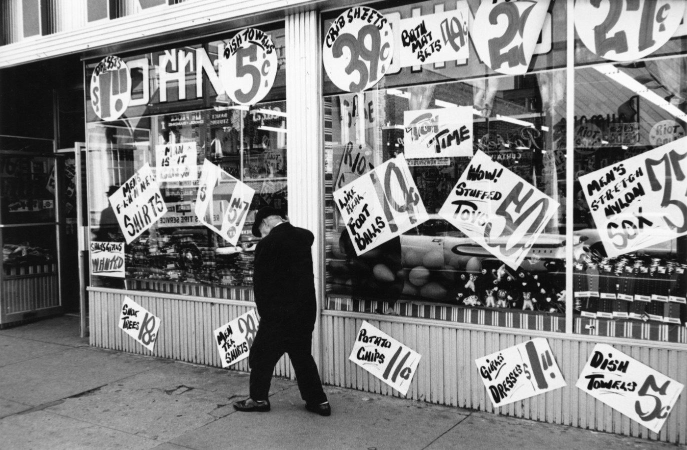 Black-and-white photograph of a man walking in in front of a storefront covered in hand painted signs advertising the prices of products