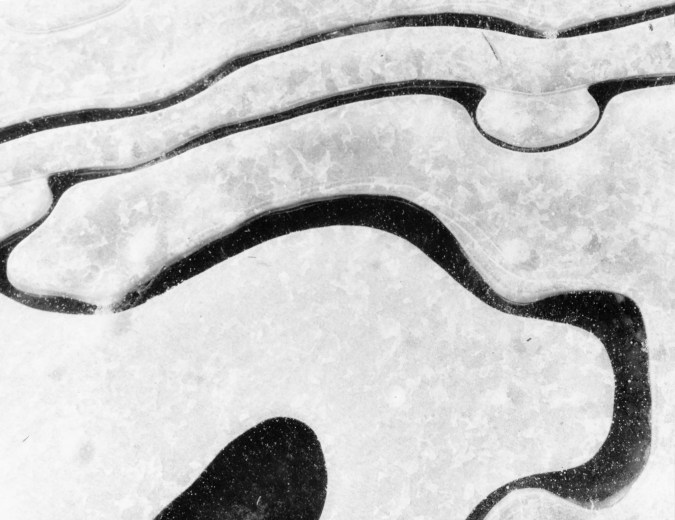 Black and white photograph of curving black cracks in ice