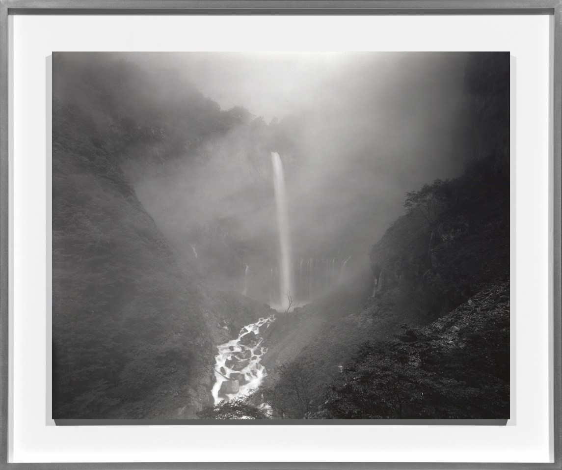Black and white photograph of a waterfall over rocky mountains through a misty haze