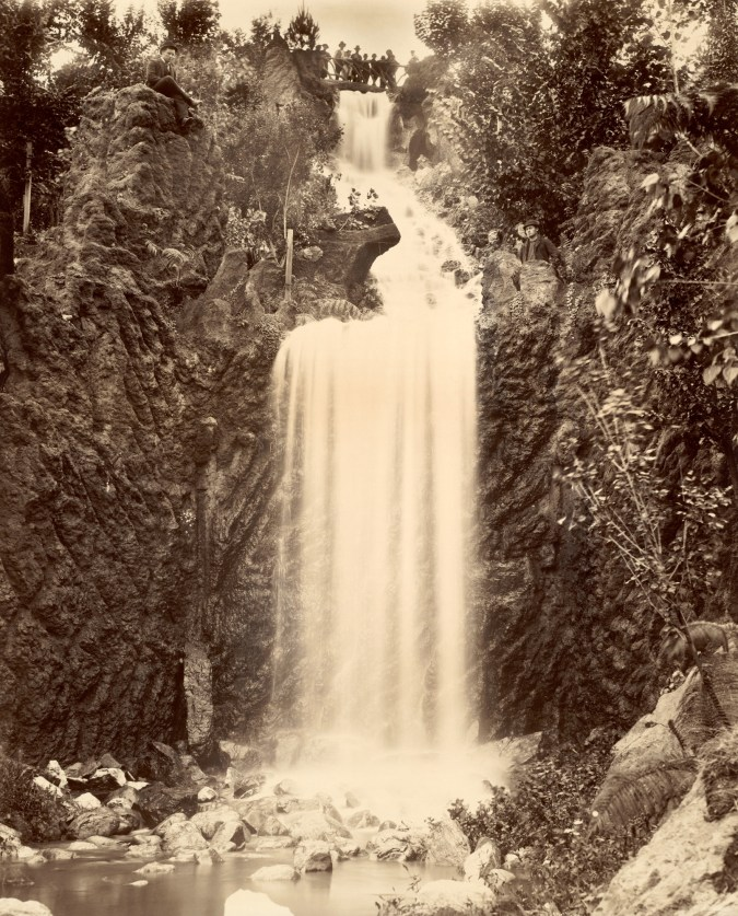 Black and white photograph of a waterfall with a gathering of people watching it from the top