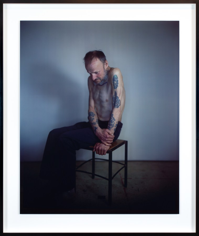 Color photographic portrait of a seated shirtless man with tattooed arms looking downwards