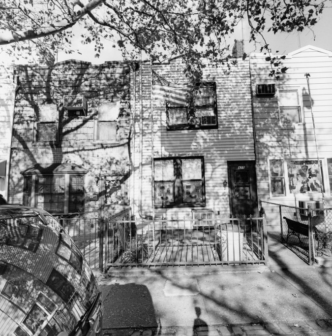 A black and white photograph of row houses with shadows from trees