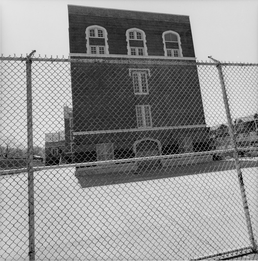 A black and white photograph of a structure behind a chain link fence