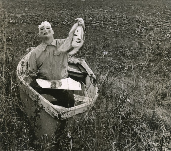 Black-and-white photograph of a person wearing a rubber mask seated in a rowboat on the grass holding up another mask
