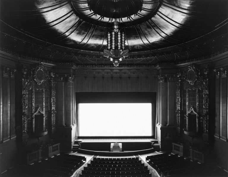 Black-and-white photograph of an empty theater with an elaborate ceiling and chandelier and a glowing white screen onstage