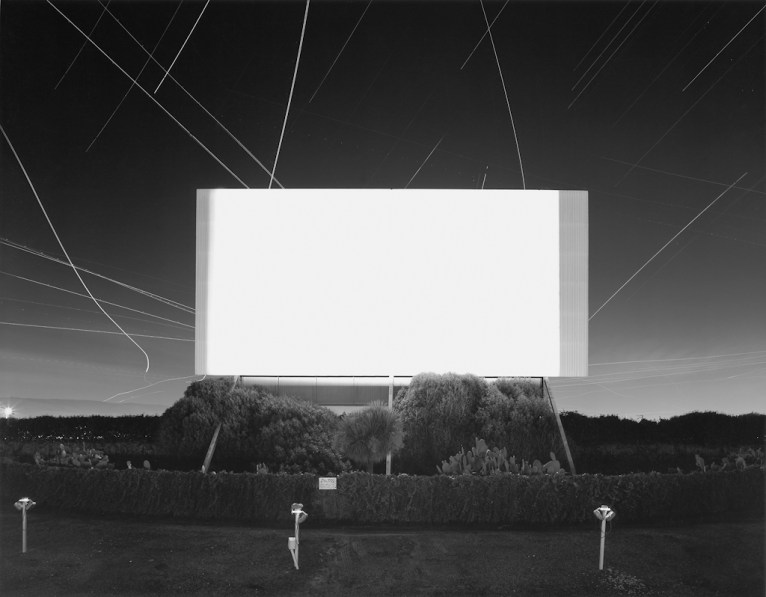 Black-and-white photograph of an empty outdoor lot at night with a glowing white screen under a sky filled with streaks of light