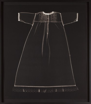 Black-and-white photograph of the faint white outline of a child's short-sleeved dress on a black background