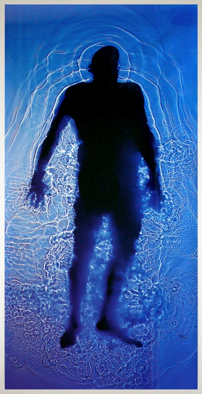 Color photograph of a man's full-body silhouette floating in a pool of transparent blue and violet liquid