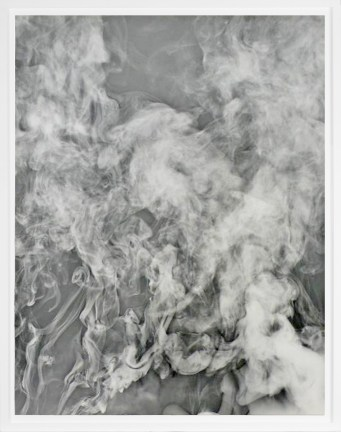 Black-and-white photograph of dissipating trails of white smoke on a gray background