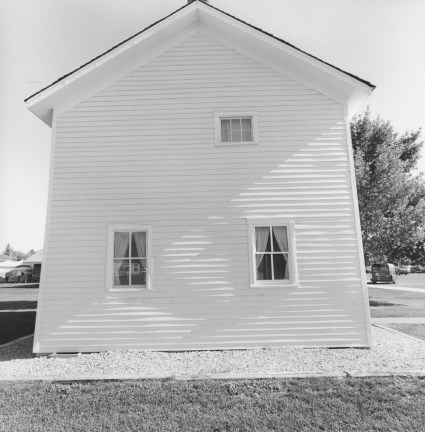 Black-and-white photograph of the side of a wooden house with three windows and a peaked roof