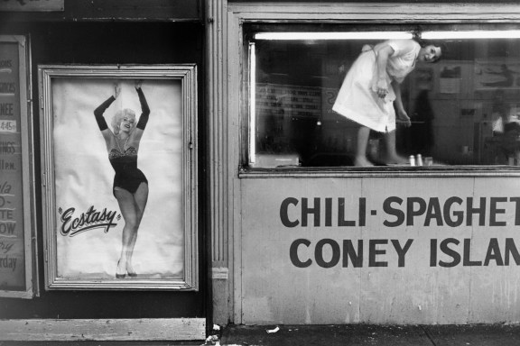 "Black-and-white photograph of woman cleaning in a window of a diner to the left is a poster of a dancing woman and the text ""ecstasy"""