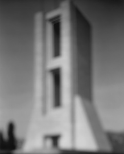 Black-and-white photograph of out of focus tower with two elongated rectangle cutouts