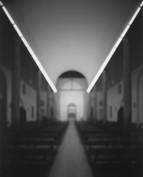 Black-and-white photograph of out of focus aisle of a church with an unadorned barrel ceiling