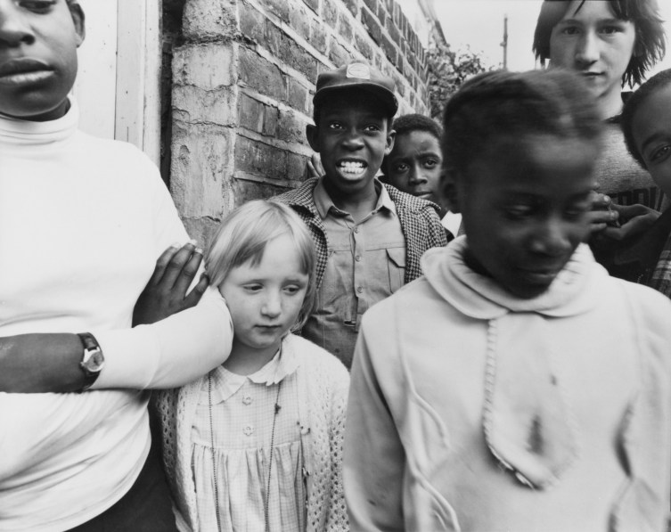 Black-and-white photograph of a group of children gathered near a brick wall