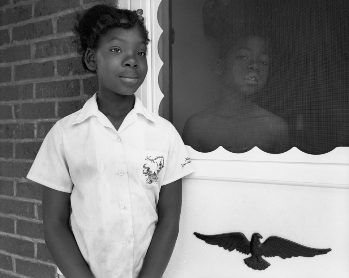 Black-and-white photograph of two children standing on either side of a screen door