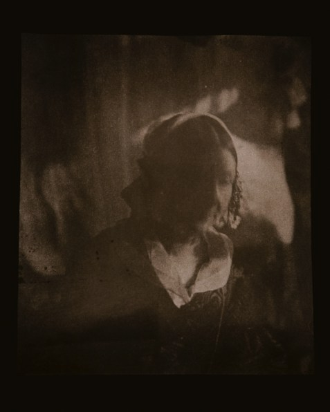 Brown-toned long-exposure photographic portrait of a woman with a blurred face and centrally-parted hair
