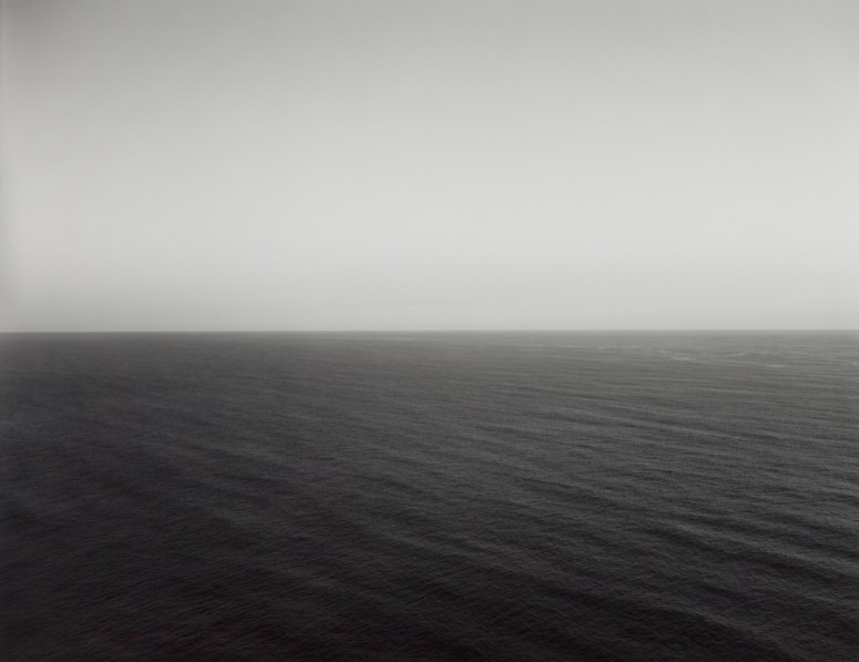 Black-and-white photograph of a calm seascape across the lower half with a hazy gray sky above