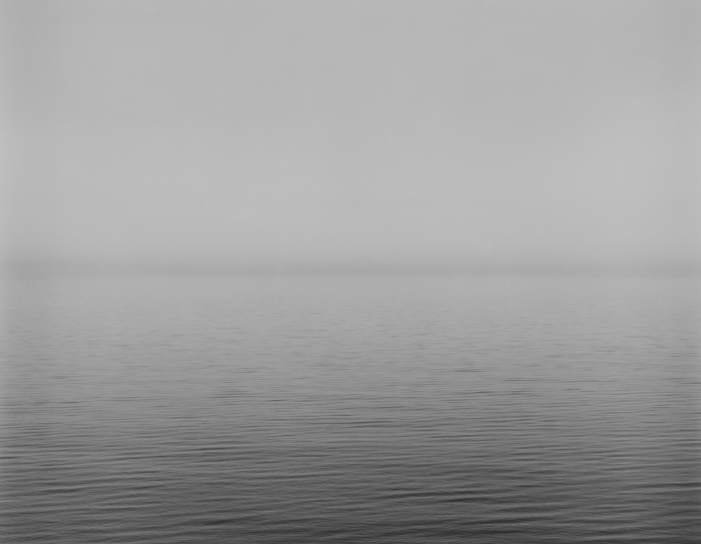 Black-and-white photograph of a calm waterscape across the lower half with a foggy sky above