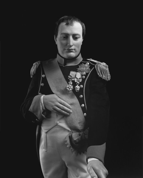 Black-and-white frontal portrait of a wax figure of a man in nineteenth century jacket with shoulder tassels, medals and a sash