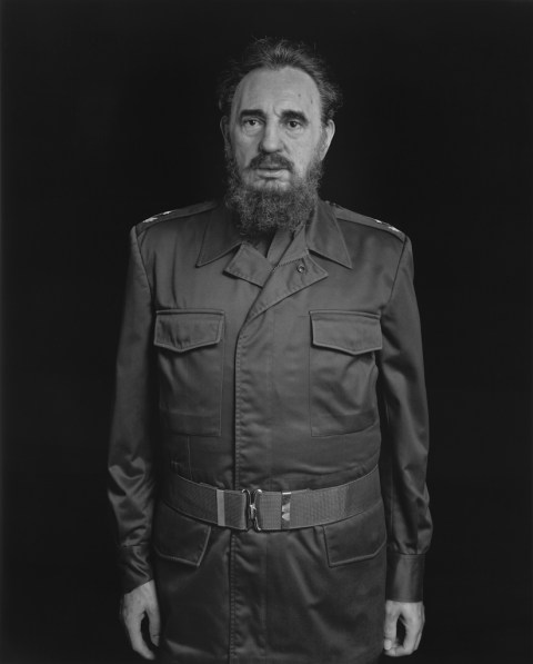 Black-and-white frontal portrait of a wax figure of a man with a beard and long military-style coat