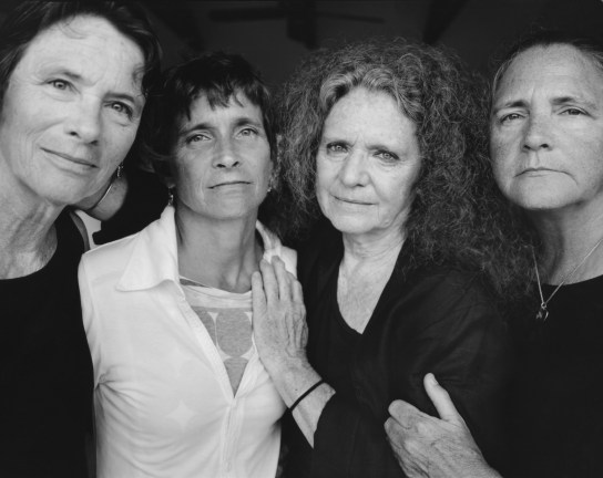 Black-and-white photographic portrait of four middle-aged women arm-in-arm