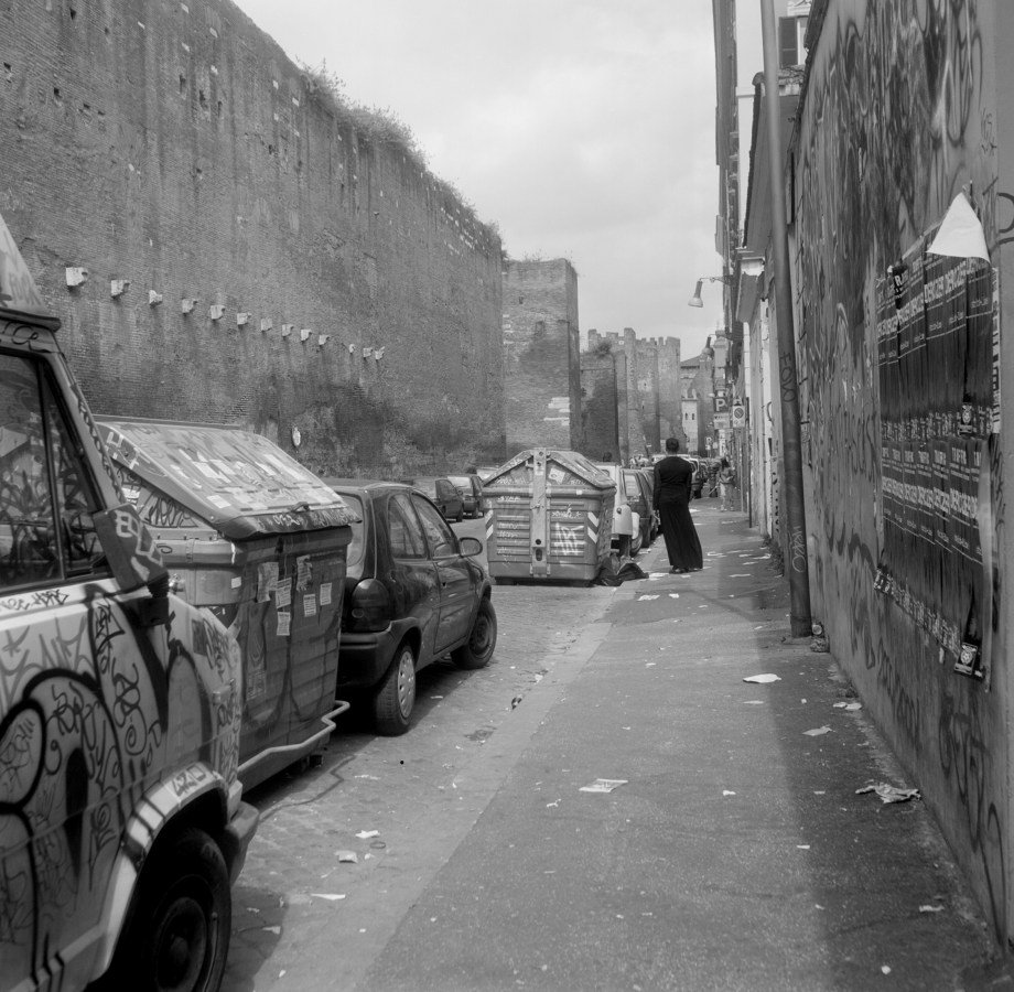 Black and white figure of a lone figure standing in a graffiti covered alleyway