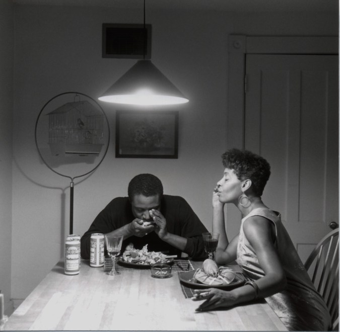 Man and woman seated at a table. He play harmonica and she closes her eyes and smokes a cigarette. In front of them are plates of lobster and cans of beer.