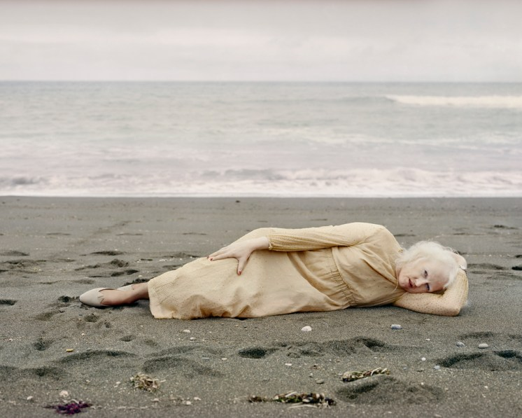 Color photograph of a woman lying on her side on wet sand before waves on the seashore