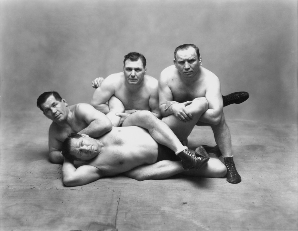 Black-and-white photograph of four wrestlers posing in crouched or laying positions