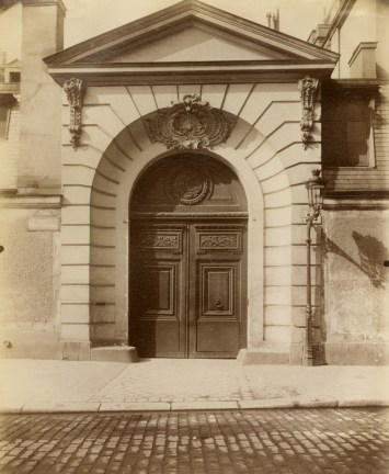 Photograph showing wooden doors with an arch on a Parisian building