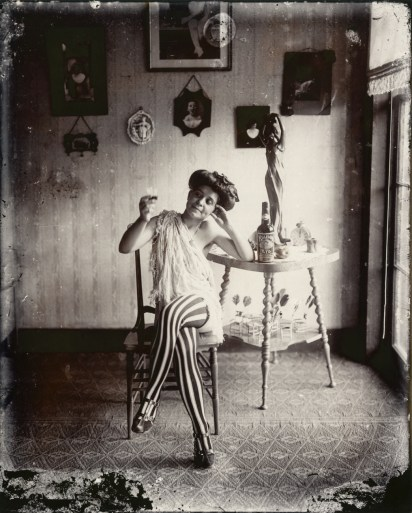 Black-and-white photograph of a woman sitting in a chair with her legs crossed